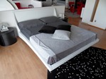 Letto imbottito rivestito in tessuto, pelle o eco-pelle, il design dinamico concilia forme morbide e carattere estroso.